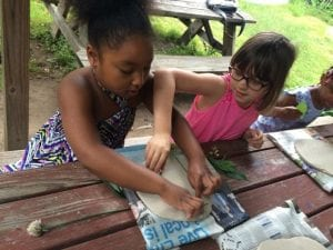Two young girls sit at a table to work on a community mural project.