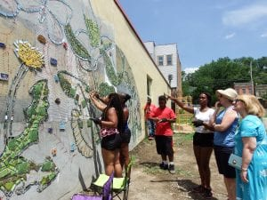Various people work to put tiles on a wall to complete a mural.