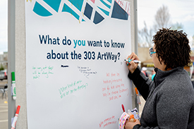 "A woman writes a question on a whiteboard that asks ""What do you want to know about the 303 ArtWay?"