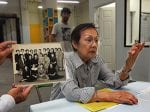 A woman tells her story about life in Little Tokyo while someone holds an old photo of her and her coworkers.