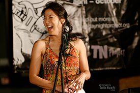 Poet traci kato-kiriyama laughs at the microphone.