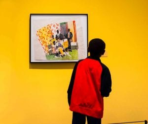 A young boy wearing a red and black jacket looks at a painting of a group of people, which is placed in a room that has bright yellow walls.