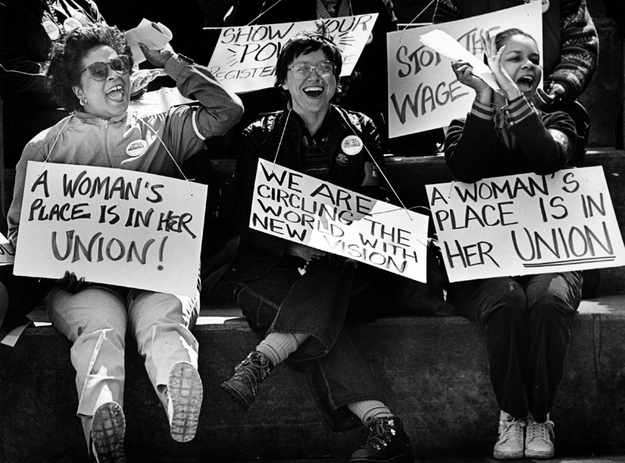 "women carrying placards saying ""A woman's place is in her union"" and other messages"