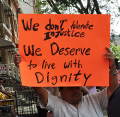 """man holding sign that says """"We don't tolerate injustice. We deserve to live with dignity."""""""