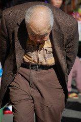 an elderly Asian man walking