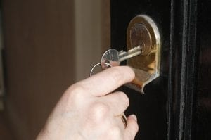 A white hand puts a silver colored key into a door lock.