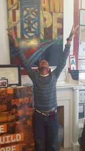 A young man who is part of a job training program in Camden, New Jersey, raises both of his arms to the air after earning a job.