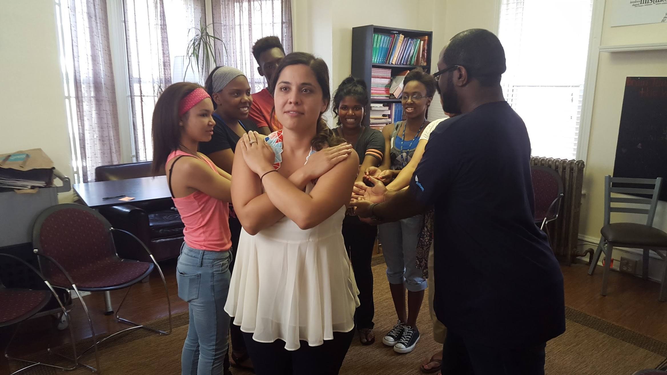 A member of a New Jersey based advocacy group crosses her hands over her chest and her fellow group members line up behind her with their arms extended. This is a trust fall.