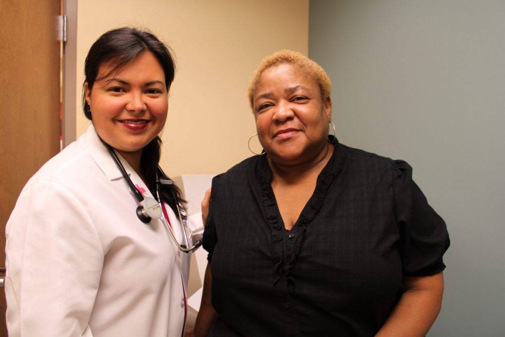 A female doctor t the Daughters of Charity Health Center in New Orleans wears a white lab coat with a stethoscope and stands next to an African American woman, who is wearing a black shirt.