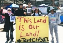 """Residents of four historically African-American neighborhoods hold up a sign that reads """"This Land is Our Land! #TentCityATL"""""""