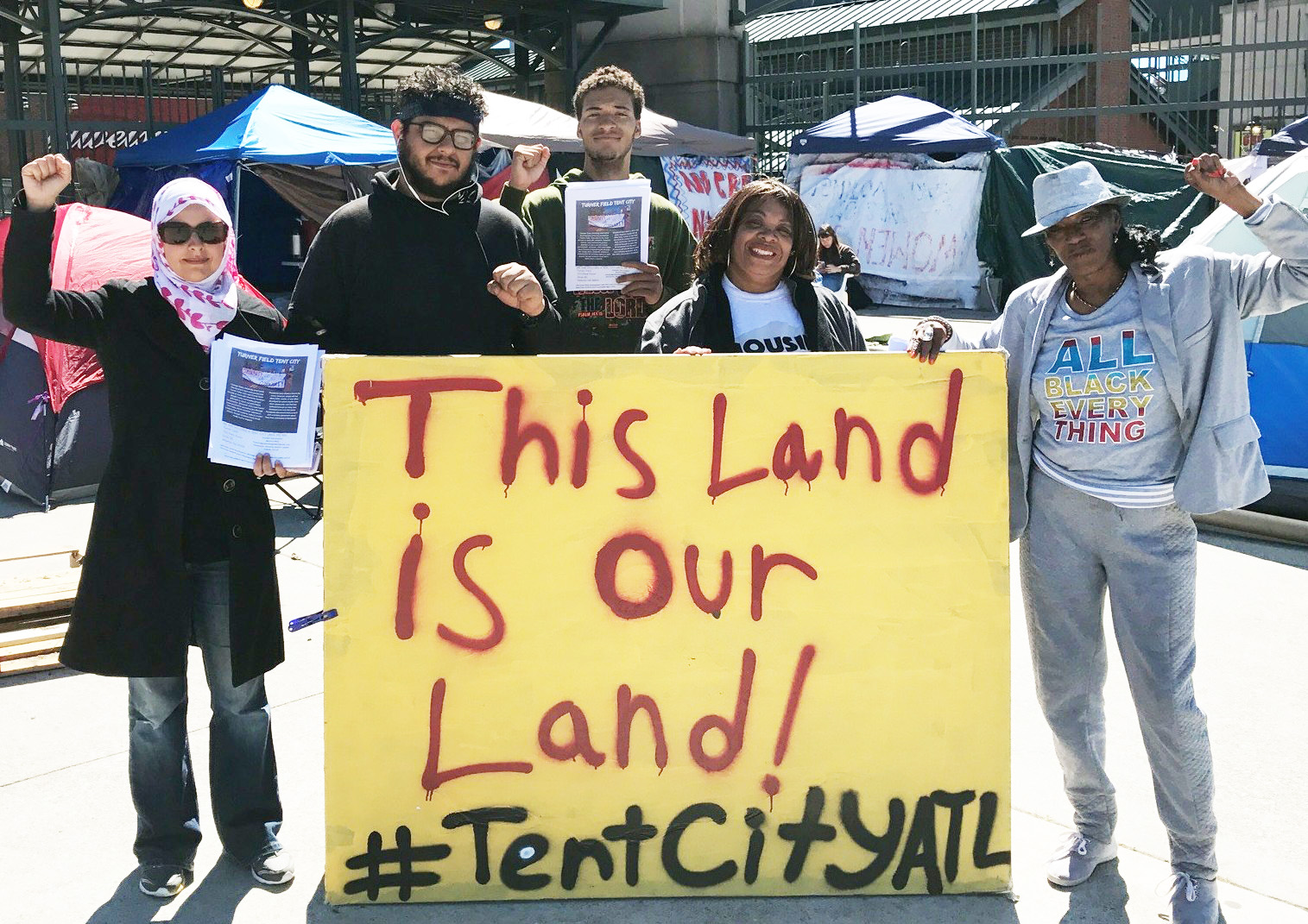 Atlanta residents hold signs protesting public-supported private development.