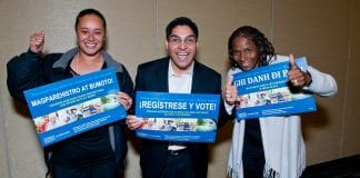 """Three members of the Non-Profit Housing Association of Northern California give a thumbs up as they hold """"Register and Vote"""" signs in different languages."""