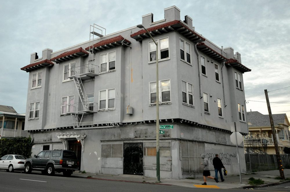 A grey-colored apartment building in Oakland California. This is an example of Naturally Occurring Affordable Housing, or NOAH.
