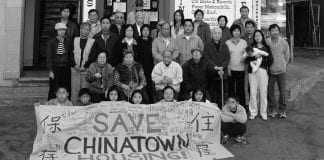 """A black and white photo of a dozen or so residents of a multifamily building standing outside with a """"Save Chinatown Housing"""" sign."""