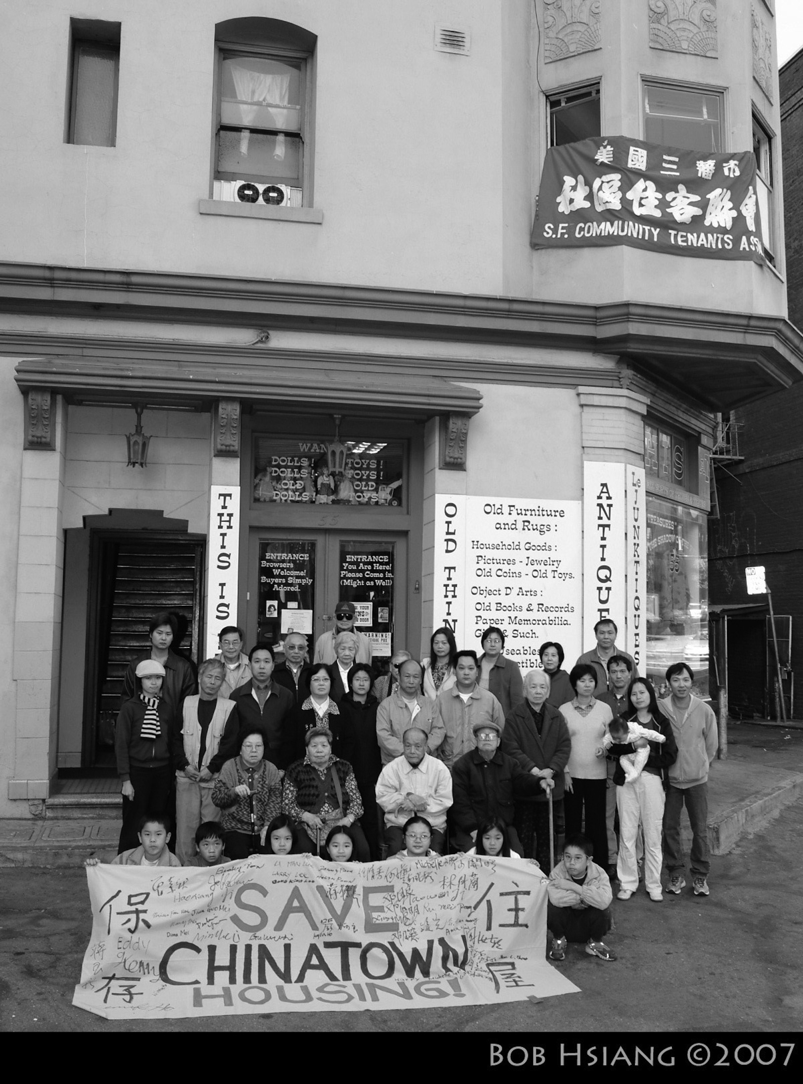 """A black and white photo of a dozen or so residents of a multifamily building who are standing outside their homes with a """"Save Chinatown Housing"""" sign. The San Francisco building eventually became a limited-equity cooperative."""