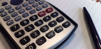 A calculator and black pen lie upon a double ruled notebook.