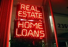 """Neon sign in window reads """"Real Estate Home Loans."""""""