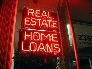 "Neon sign in window reads ""Real Estate Home Loans."""