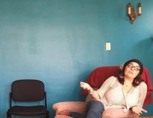Adela Nieves sits on pink chair in front of a blue wall.