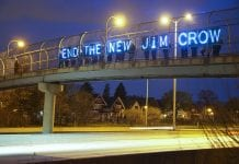 """On an overpass over a highway, people hold a lighted sign that reads """"End the New Jim Crow."""""""