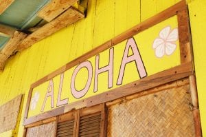 Yellow sign reading 'Aloha.'