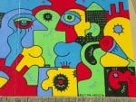 An abstract mural in red, blue, green, yellow, and black.