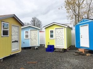 Front of four small houses, colored tan, light blue, yellow, and deep blue with a door and one window.