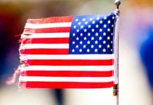 Small American flag with fringed edges attached to a wire stick.