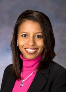 Angela Mingo poses for a headshot wearing a black blazer and a pink turtle neck shirt.