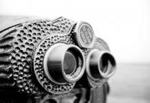 Close-up black and white photo of binoculars.