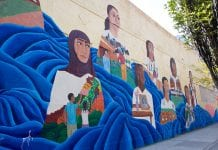Mural on wall with faces of girls looking into the distance.