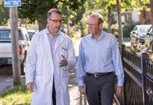 Dr. Kelly Kelleher and the Rev. John Edgar walk down a street in Columbus, Ohio.