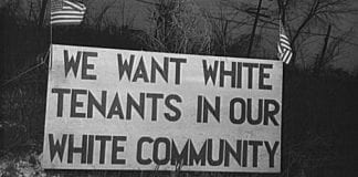 """A black and white photograph from 1942 of a sign that read """"We want white tenants in our white community."""""""