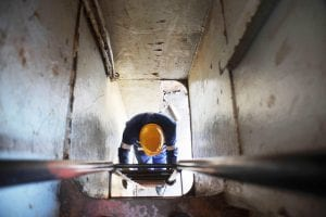 View of a worker's hard hat as they climb on a ladder in a tunnel.