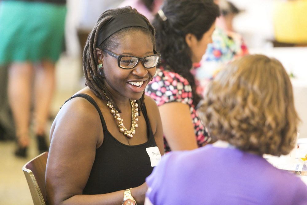 An African-American woman chats with another woman at at the Metropolitan Area Planning Council's State of Equity in Metro Boston event in 2014.