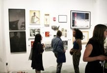 Patrons looking at gallery wall.