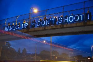"""Neon """"Hands Up-Don't Shoot"""" sign displayed on highway overpass."""
