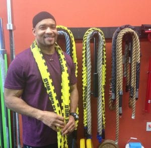 An African-American man smiles in his gym, which he opened thanks to a loan he received due to his character, not his credit score. Character lending is gaining steam again.