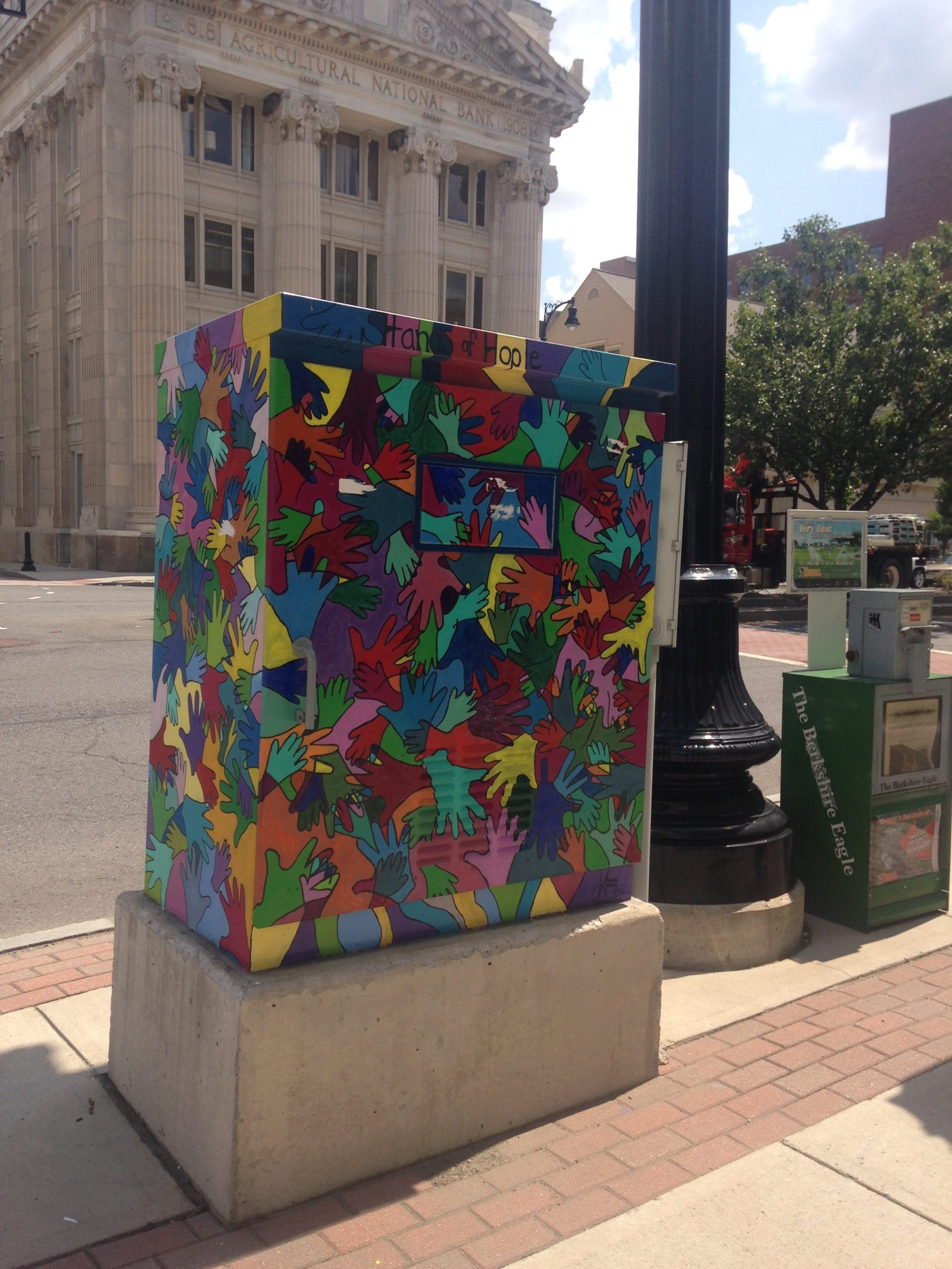 Art in Pittsfield, Massachusetts: A utility box on a sidewalk is covered with interlocking hands in all the colors of the rainbow.