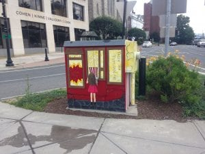 A utility box in a traffic median painted to look a street vendor of popcorn with a child standing in front.