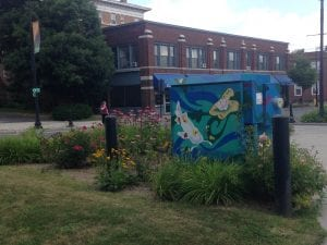 A utility box painted blue with stylized fish sits in a flower bed in a park with a brick factory-style building in the background
