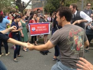 """A white man is dancing in the foreground with someone who is out of the frame, in front of a red banner reading """"Vinage Dance, Not Vintage Values"""" and """"Swing Dancers for Justice and Equality"""""""