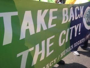 """A green and blue banner with the words """"Take back the city"""" and part of a logo visible on the right side."""