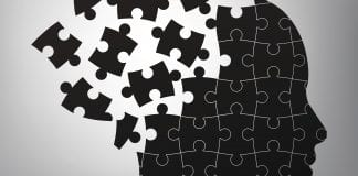 A black and white illustration of a head broken into puzzle pieces.
