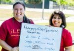 """Two woman hold a sign that reads, """"Pedagogy of the Oppressed Taught me ..."""""""