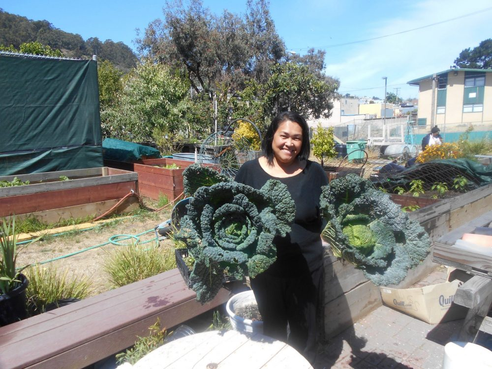 A woman holds two large lettuces that were grown in a garden attached to a public housing location in San Francisco.