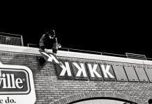 Man places strikeout symbols on baseball stadium wall.