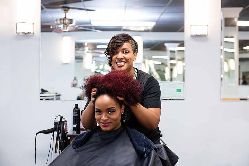 A stylist at a salon works on another woman's hair at a salon in North Carolina. The business, Essence of Beauty, secured a loan thanks to the help of a CDFI.