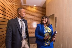 Two employees of Grace Federal Solutions in North Carolina, an African-American man and woman, chat in the hallway of their offices. The company secured a loan from a CDFI.