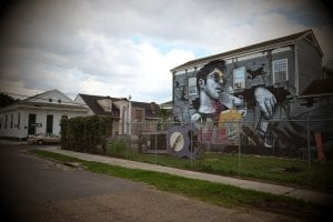 """A sprawling white """"hipster"""" is memorialized against a backdrop of romanticized visions of blight in a mural that dominates an intersection in the historically Black 7th Ward in New Orleans."""